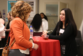 Two female students at La Roche University network at the Etiquette Dinner & Professional Mixer hosted by Student Academic Support Services.