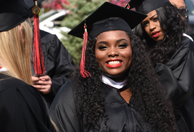 Female student smiling and wearing cap and gown on graduation day at La Roche University