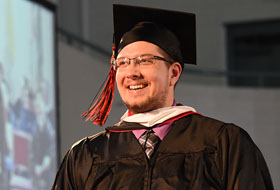 Male graduate student walking and smiling