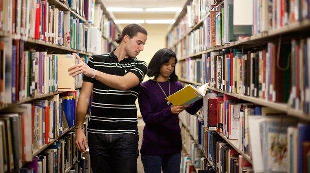 2 students looking for books in library