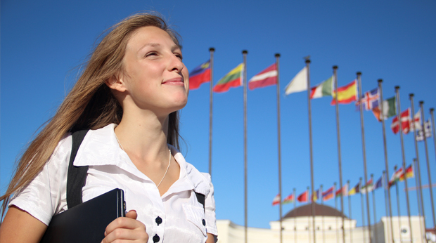 Female with international flags on flag poles in background