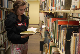 Female student standing in isle of books reading