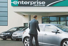 Man walking toward a car at an Enterprise dealership