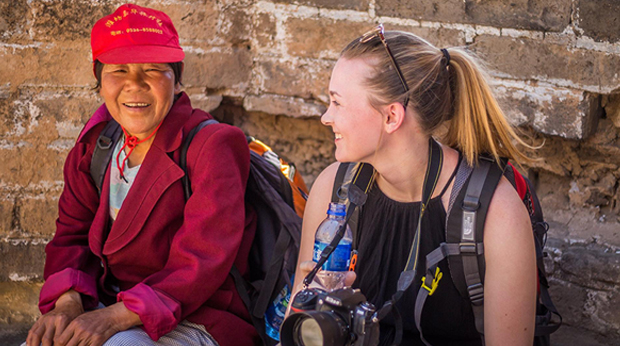 Student Olivia Healy sitting with woman on a study abroad trip