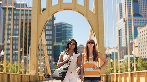 Two female students standing on bridge in downtown Pittsburgh